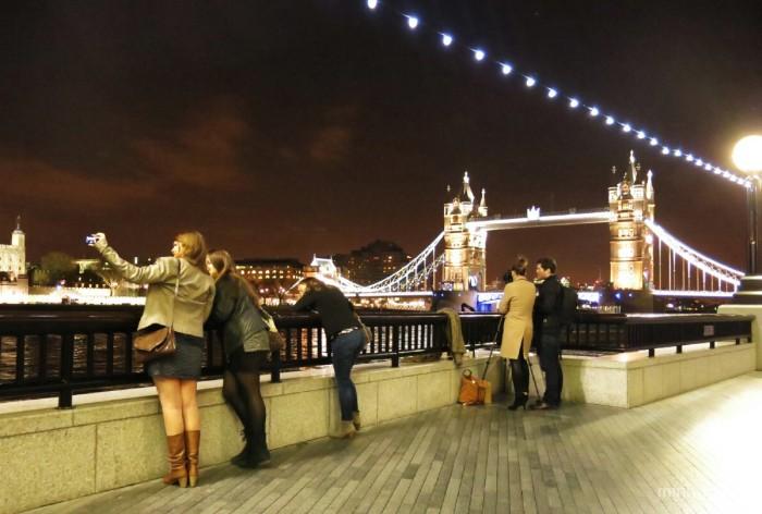 _Du khach tu tap chup anh ben bo song Thames (xa xa ben phai la Tower Bridge)